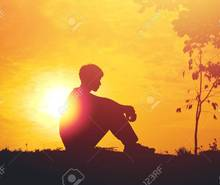 68483843 silhouette of a young boy sitting sadly on sunset